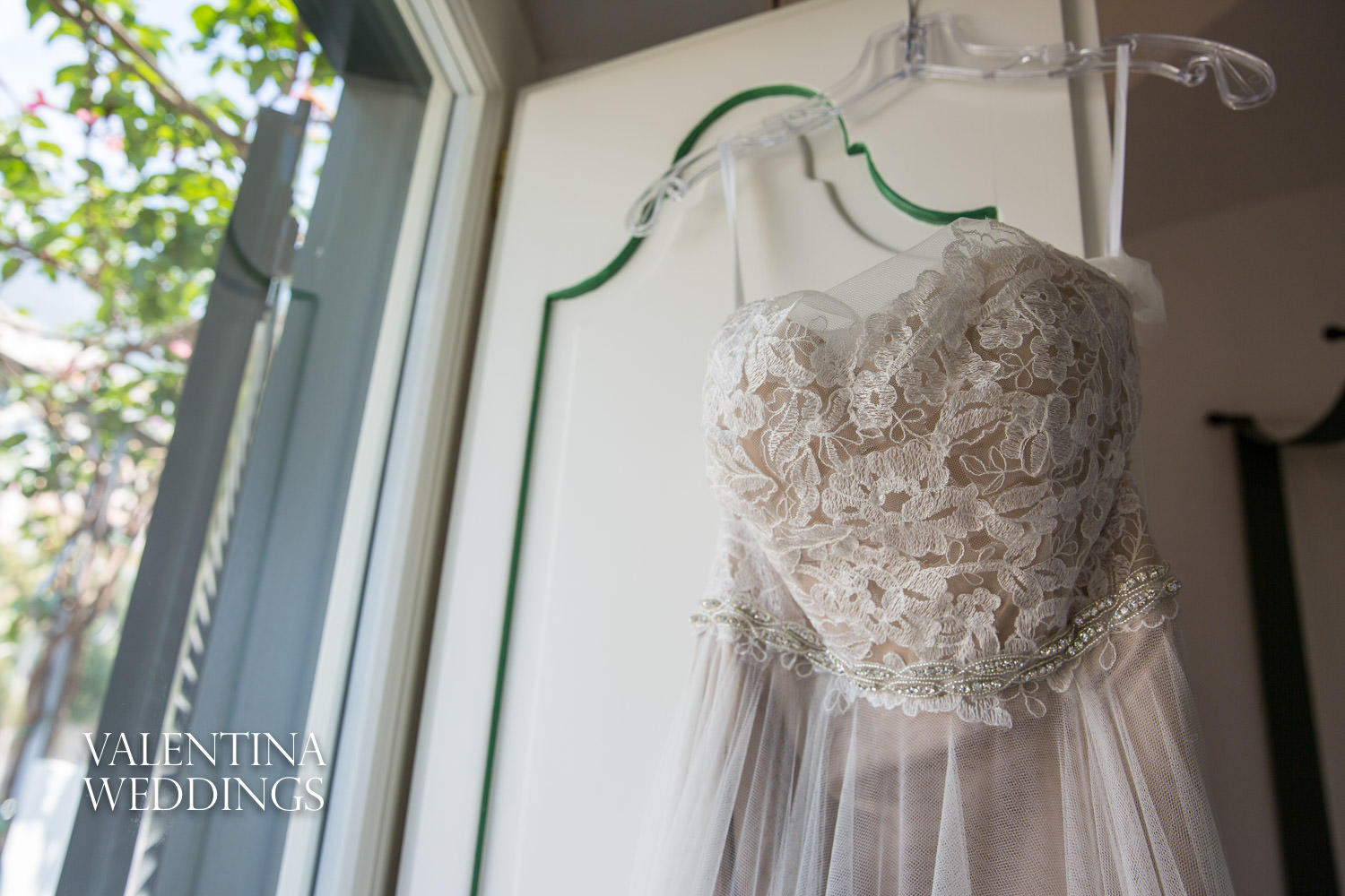 Wedding dress hanging in window of Palazzo Murat